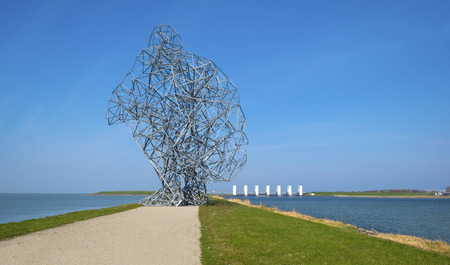 Dike with sculpture in a lake under a clear sky Stockfoto