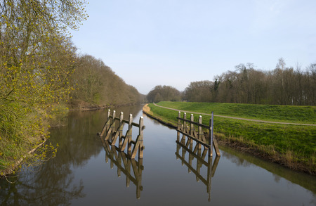 bollards: Bollards reflecting in a river under a clear sky Stock Photo