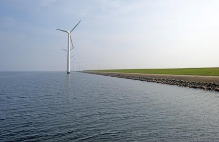 Wind turbines in a lake along a dike photo