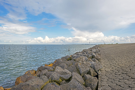 markermeer: Clouds over a dike in a lake
