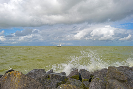 markermeer: Clouds and storm over a dike in a lake Stock Photo