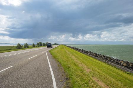 markermeer: Road on a dike along a lake Stock Photo