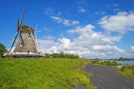 dike: Windmill on a dike under a blue sky Stock Photo