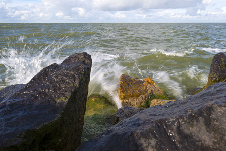 markermeer: Basalt stones in a stormy lake at fall Stock Photo