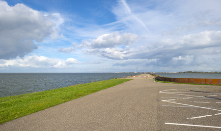 markermeer: Clouds over a dike along a lake at fall