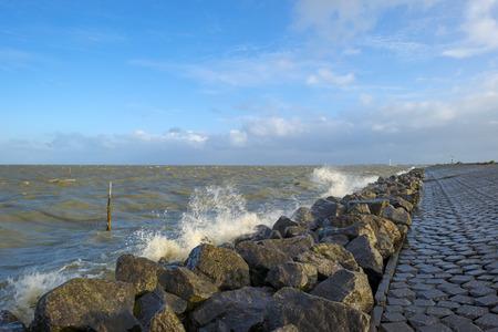 Basalt stones along a dike in a stormy sea Stockfoto