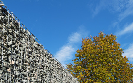 tight filled: Wall of steel and stones in sunlight