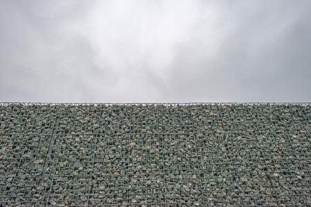 tight filled: Wall of steel and stones under a grey sky at fall