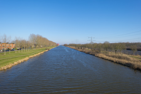 flevoland: Canal separating houses and a rural area in winter Stock Photo