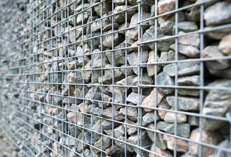 tight filled: Wall of steel and stones in winter