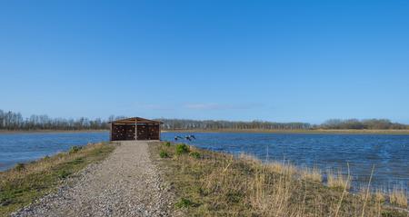vogelspuren: Vogelbeobachtungsh�tte am Ufer eines Sees Lizenzfreie Bilder