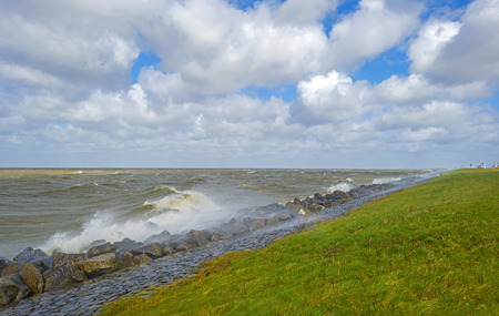 raging: Storm raging over a lake along a dike in spring