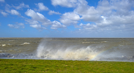gust: Storm raging over a lake along a dike in spring
