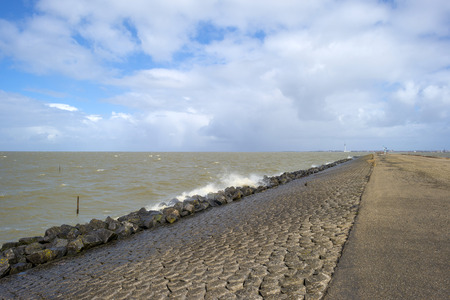 markermeer: Storm raging over a lake along a dike in spring