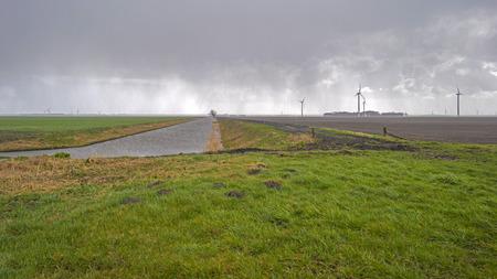 rain shower: Rain shower over a canal through farmland
