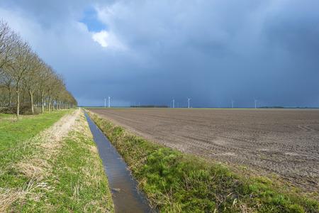 rain shower: Rain shower over plowed land in spring