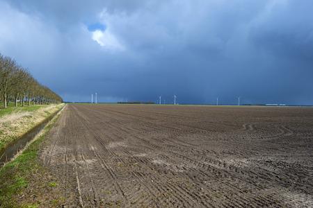 plowed field: Plowed field under a rain shower in spring