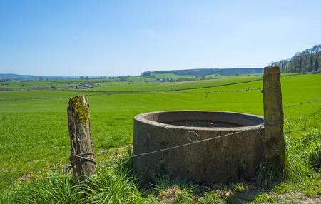 cisterna: Cisterna con agua en un meadwo soleado en primavera Foto de archivo