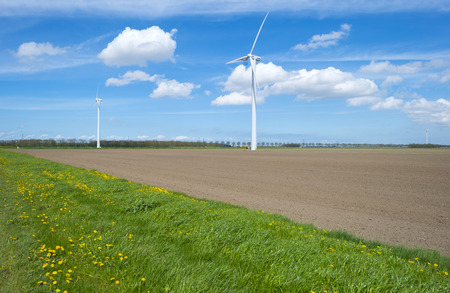 plowed field: Two wind turbies in a plowed field in spring