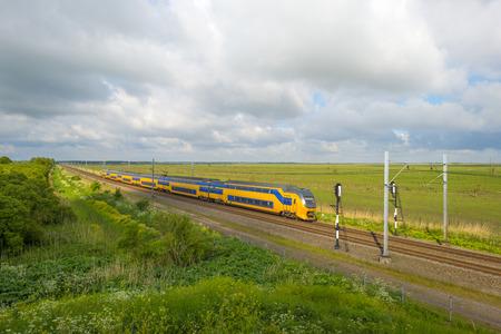 gloriole: Tren el�ctrico caballo a trav�s de un paisaje soleado en primavera Foto de archivo