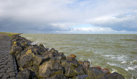 markermeer: Deteriorating weather on a dike along a sea in spring