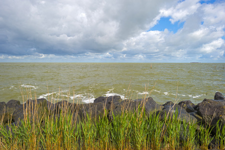 deteriorating: Deteriorating weather on a dike along a sea in spring
