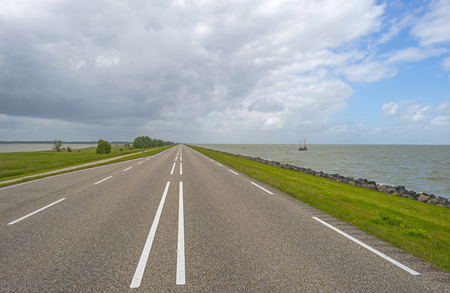 markermeer: Road over a dike under a blue cloudy sky Stock Photo