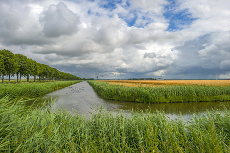 deteriorating: Canal through sunny farm land in deteriorating weather