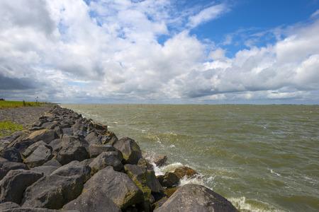 markermeer: Basalt rocks protecting a dike along the coast of a sea