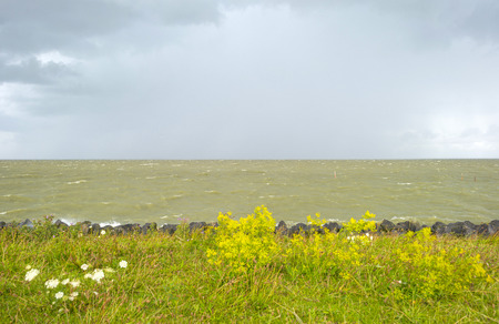 markermeer: Deteriorating weather on a dike along a sea