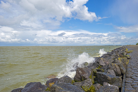markermeer: Deteriorating weather on a dike along a sea in summer