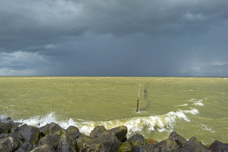 downfall: Deteriorating weather on a dike along a sea in summer