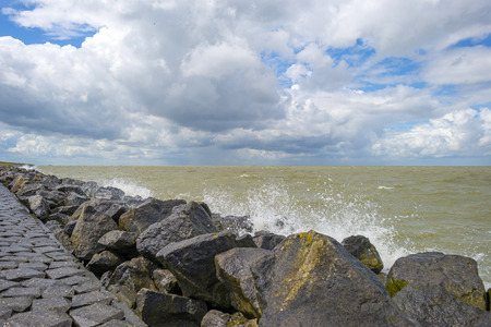deteriorating: Deteriorating weather on a dike along a sea in summer