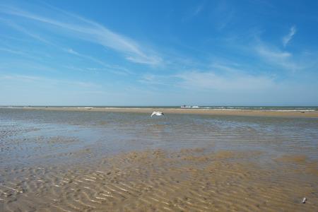 Blauwe bewolkte hemel op een strand langs de zee