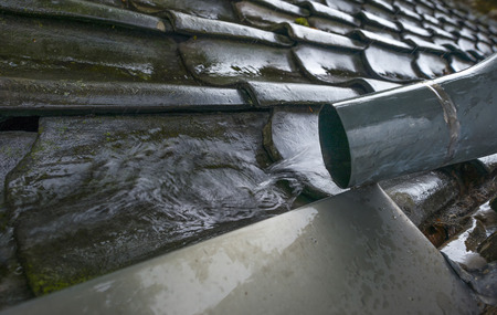 drainage: Water drainage from a roof falling on a rainshower