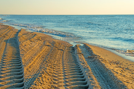 ending: Tire tracks on a beach ending in sea Stock Photo