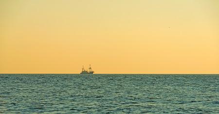 trawler: Fishing trawler at sea at sunset in autumn