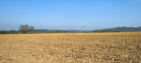 hilly: Railroad along a hilly plowed field in spring Stock Photo