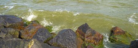 dike: Waves along a dike of basalt stones Stock Photo