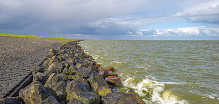 markermeer: Cloudy sky above a dike along a lake in spring