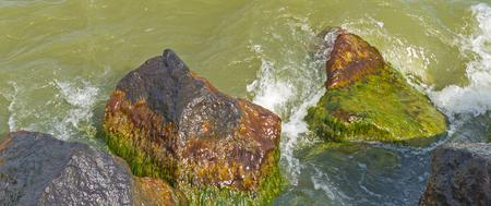 basalt: Waves along a dike of basalt stones Stock Photo