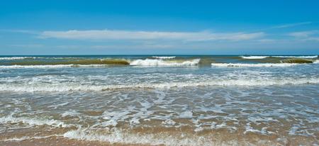Waves of a sea below a cloudy sky