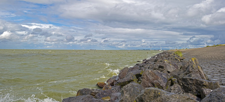 markermeer: Clouds over a dike along a lake