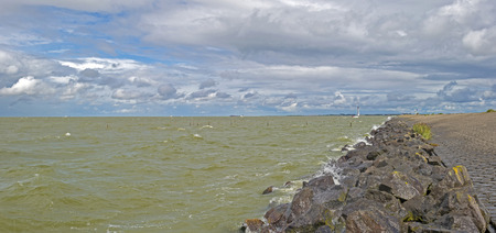 lelystad: Clouds over a dike along a lake