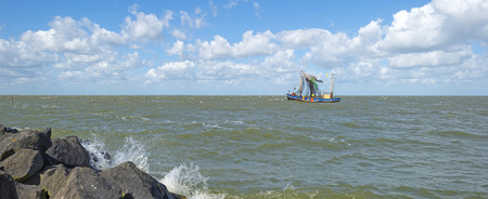 markermeer: Trawler fishing in a lake along a dike