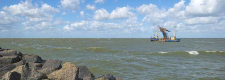 trawler: Trawler fishing in a lake along a dike