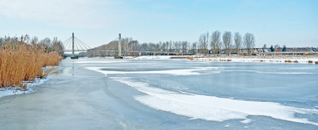 ice sheet: Bridge over a frozen canal in winter Stock Photo