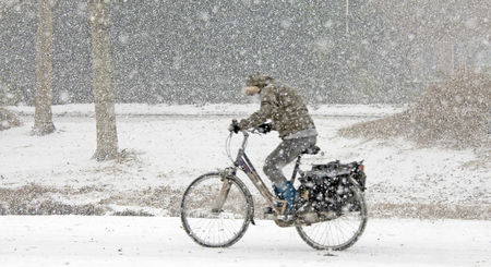 Cyclist biking through the snow in winter