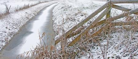 ice sheet: Wooden fence in a frozen landscape in winter