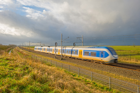 deteriorating: Electric train in sunny deteriorating weather